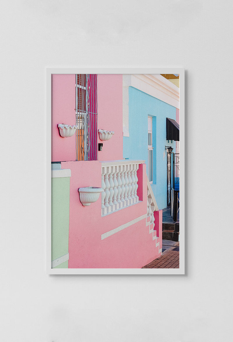 image of photo of green, pink and blue homes with white railings and framing in white frame on white wall.