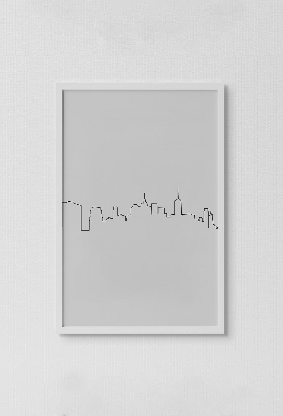 image of print of stencil drawing of city skyline in black lines with white background in white frame on white wall.