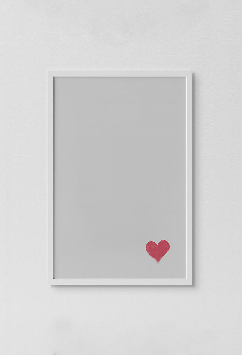 image of single red heart in right bottom corner of print on white background in white frame on white wall.