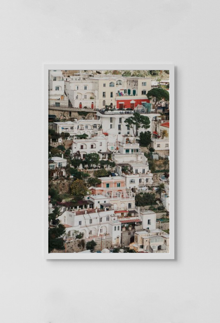 image of photograph of European city with multi-colored homes in white frame on white wall.
