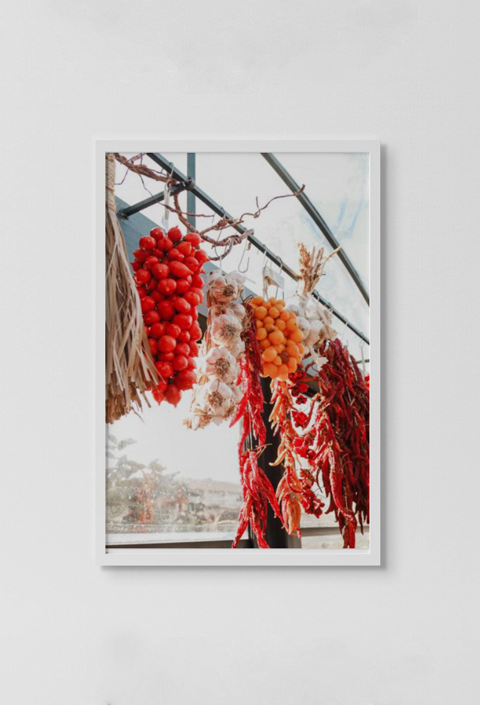 image of photograph of fresh spices hanging at market with sky in background in white frame on white wall.