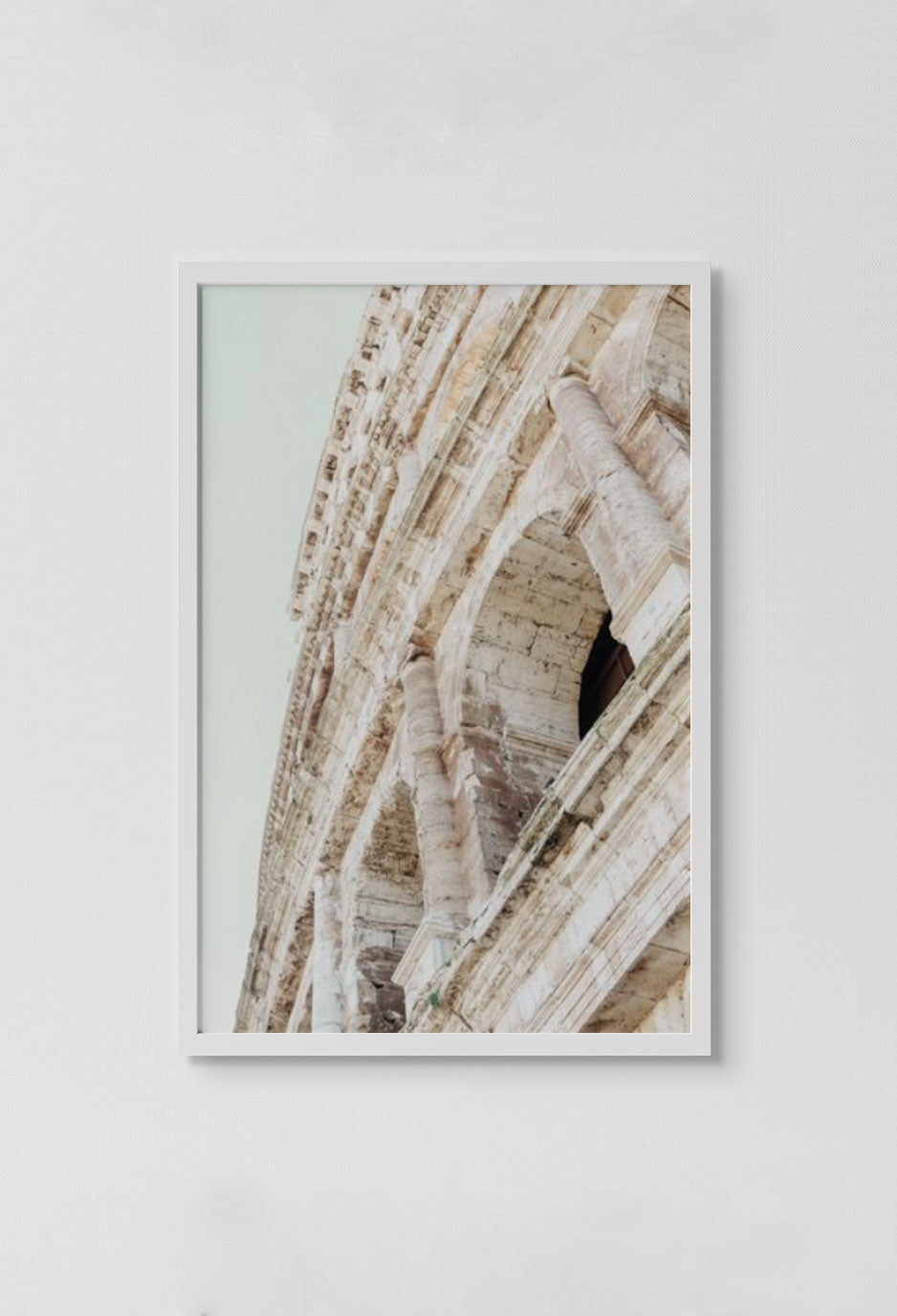 image of photograph of outside of coliseum windows looking up with sky in background in white frame on white wall.
