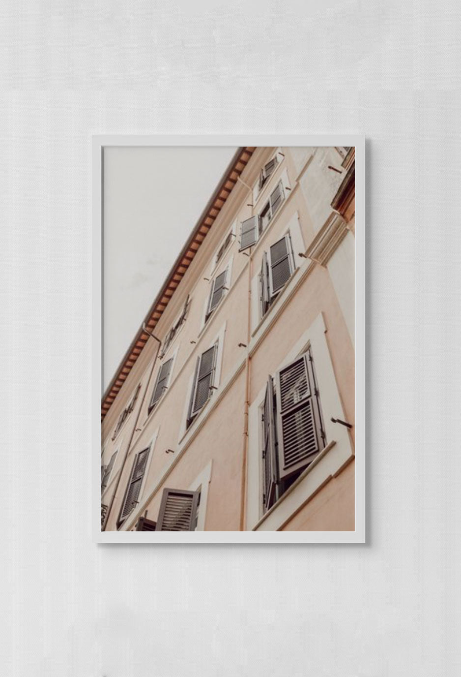 image of photograph of several French windows with windows open and sky in background in white frame on white wall.