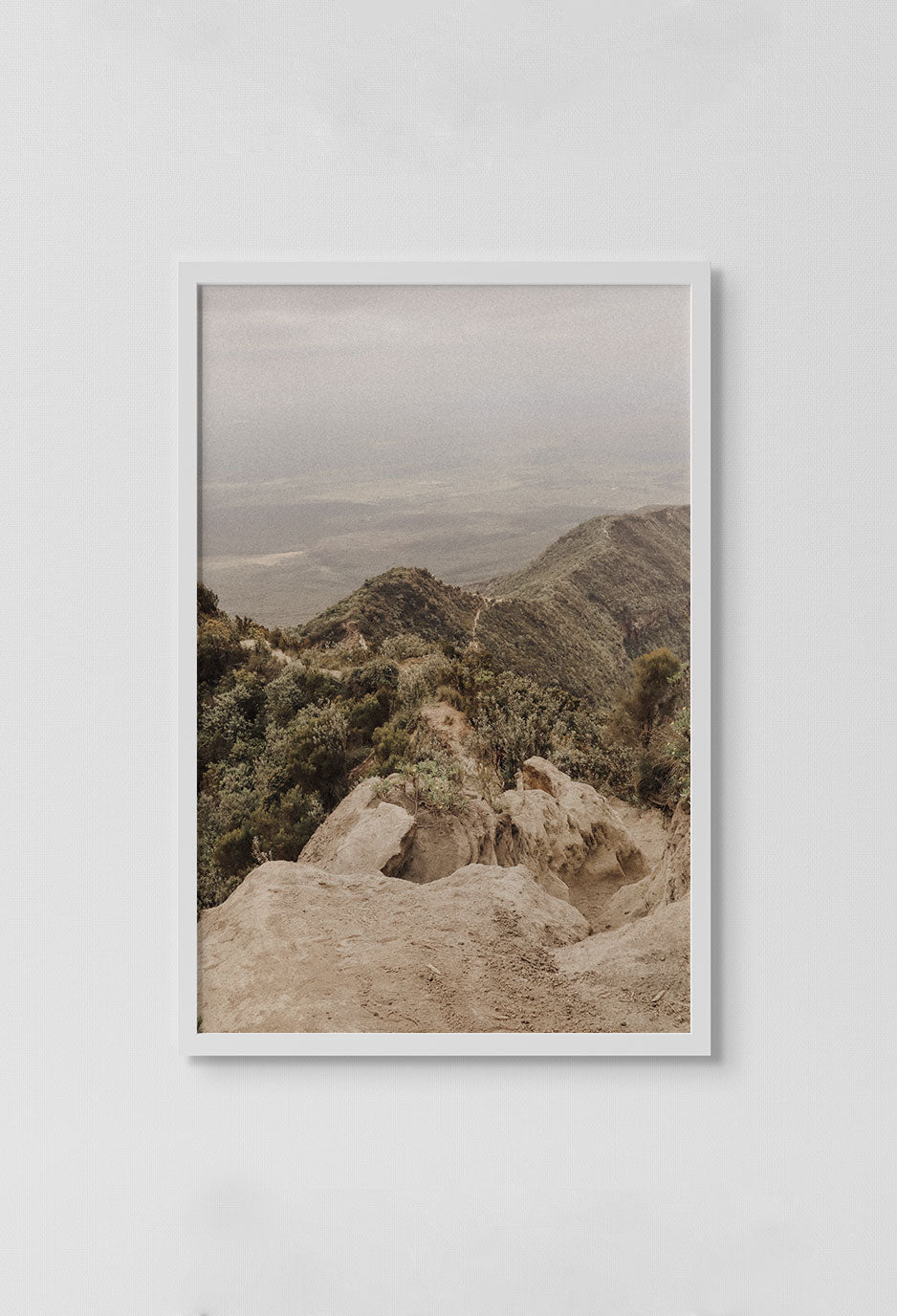 image of photograph of mountain top with trees and valleys in the water in white frame on white wall.