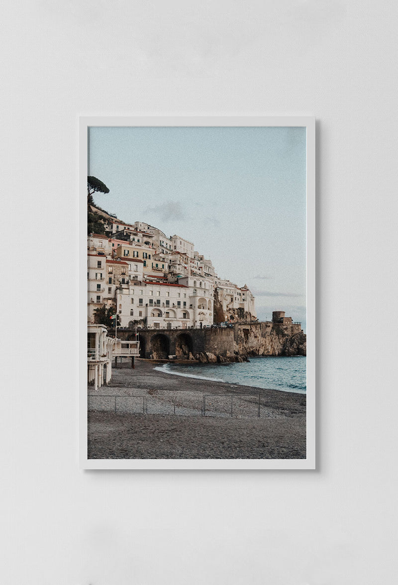 image of photo of city by beach on top of cliff over ocean in white frame on white wall.
