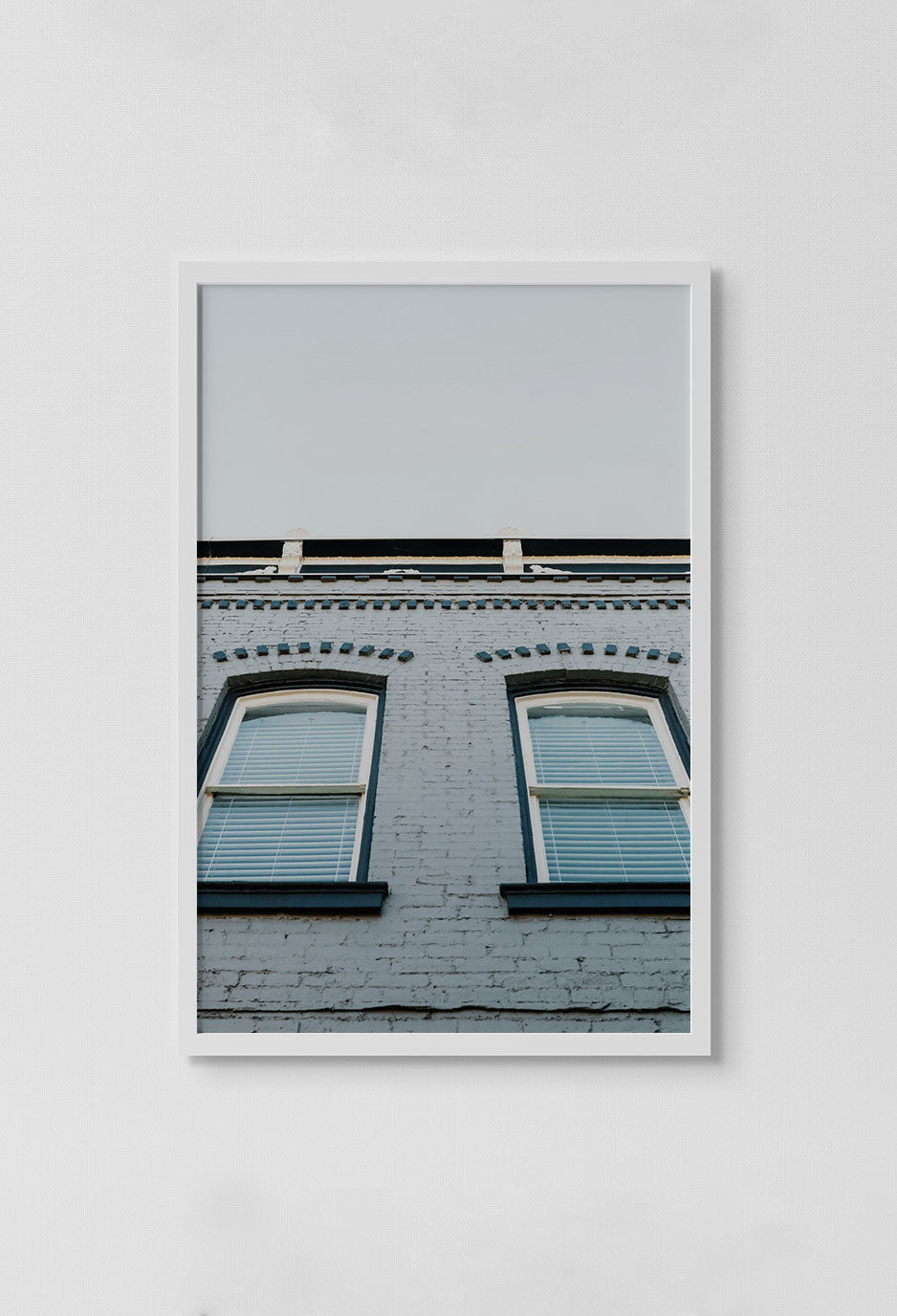 image of photo of building windows and sky in white frame on white wall.