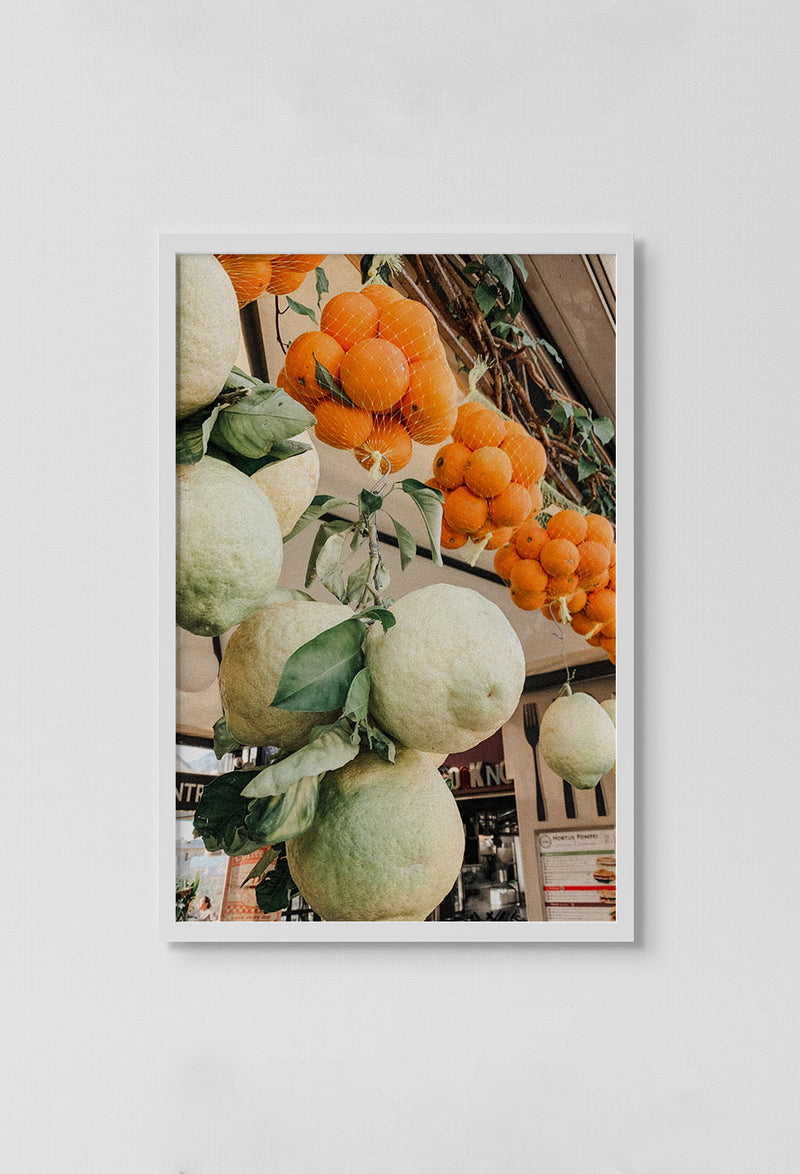 image of photo of fruit hanging from tent in market in white frame on white wall.