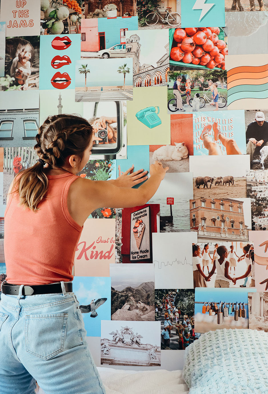 girl standing in room placing images on wall to create collage
