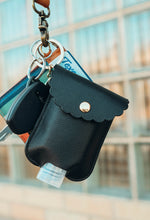 close up image of black hand sanitizer case attached to key ring with keys and wallet