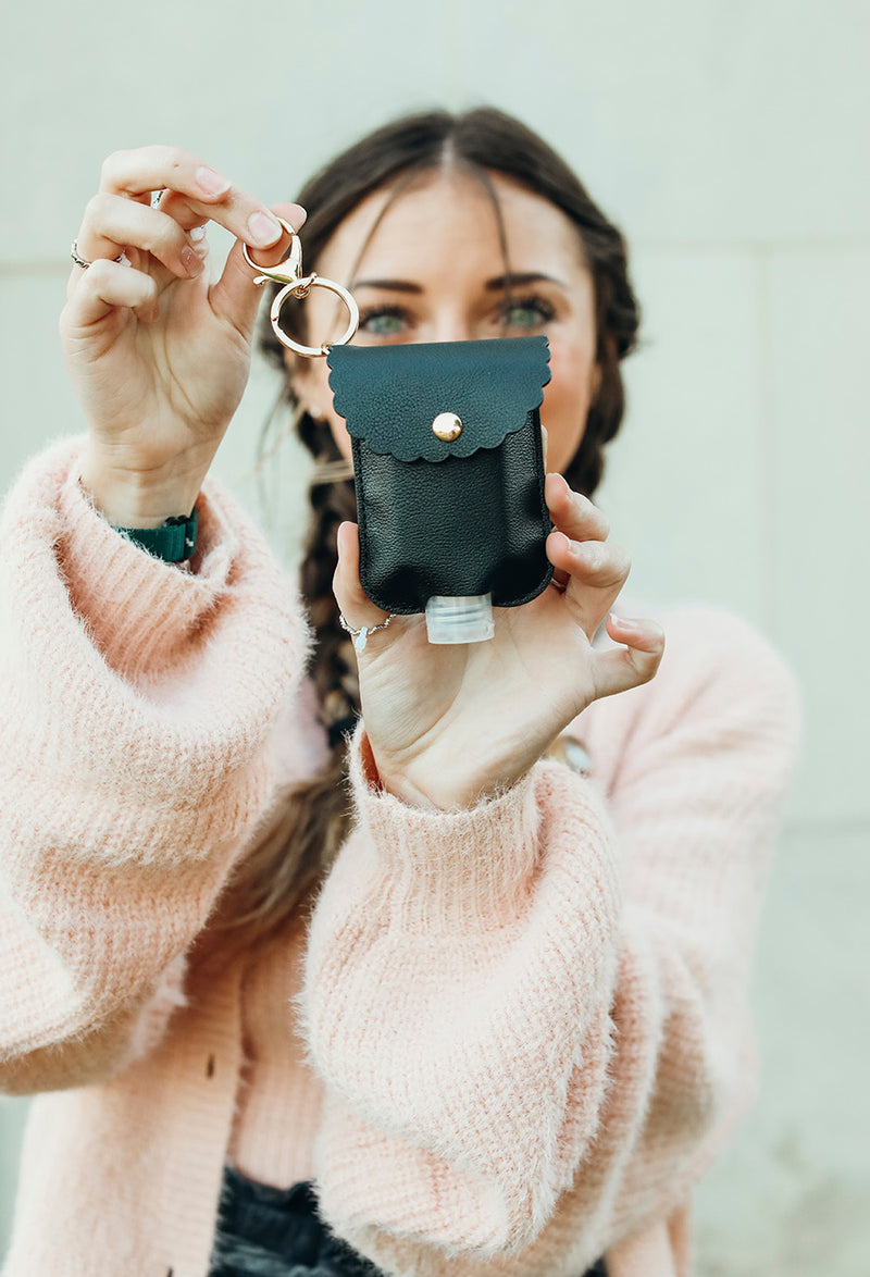 girl  holding up black hand sanitizer case showing keychain