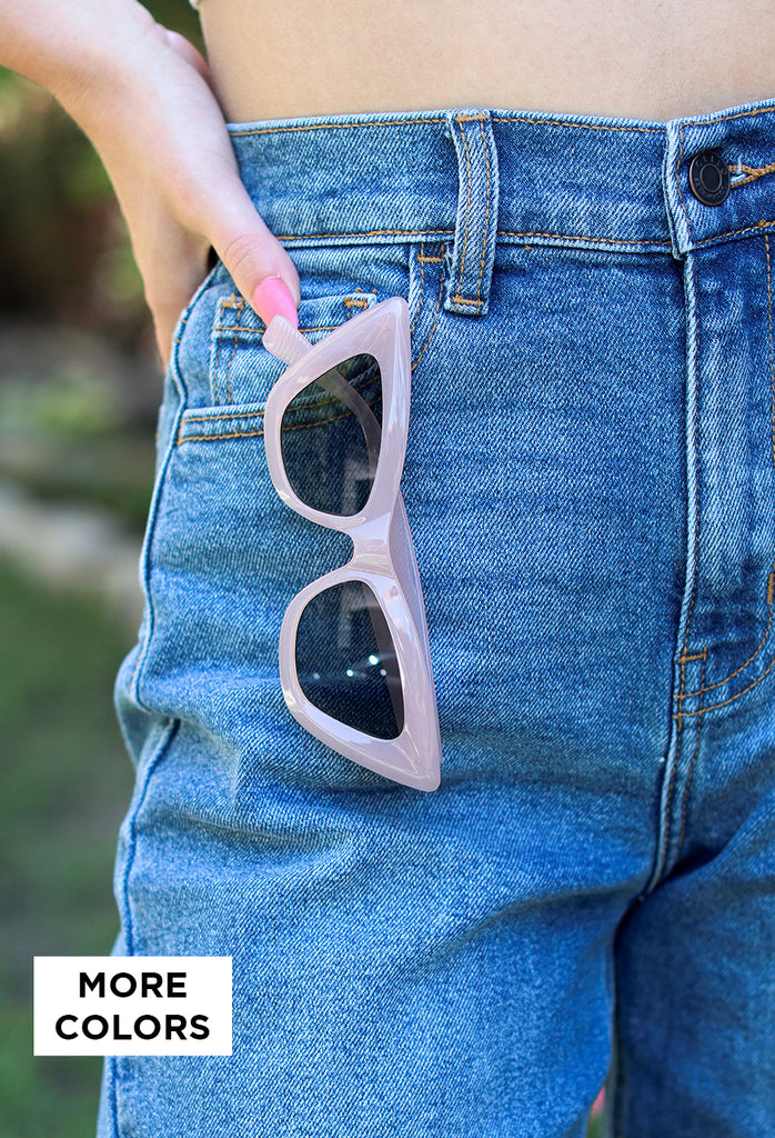 girl wearing black speckled beanie with puff ball and flannel jacket smiling looking away from camera