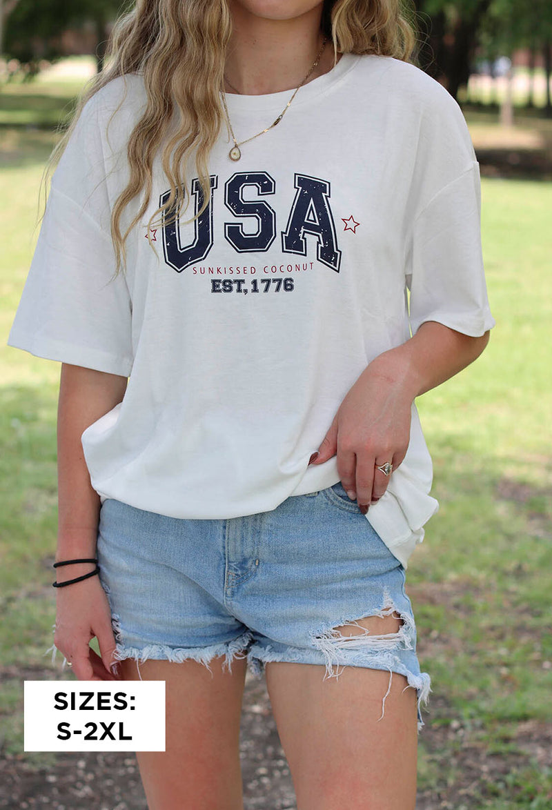 girl wearing black bandana print face mask looking at camera