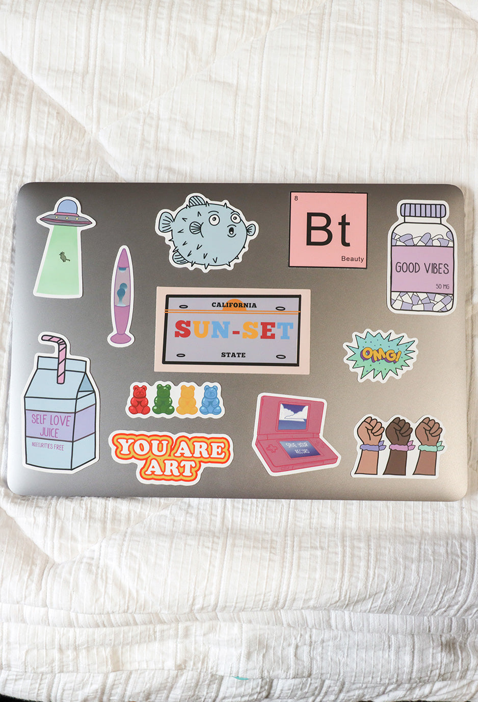 12 bright colored stickers on laptop in various shapes