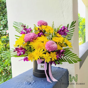 Condolence flower with Yellow Chrysanthemum, Purple Orchid, Purple Ball Chrysanthemum and foliage with Round Shape Box