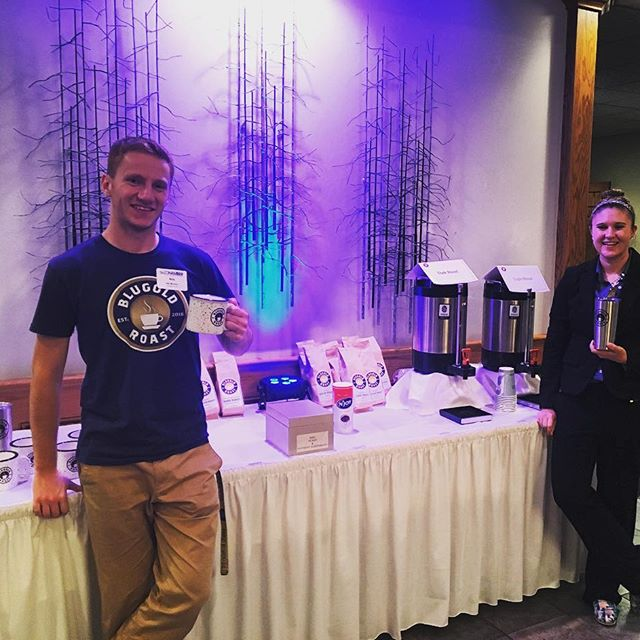 Nils Mowlem & Meghan Hoag pose in front of table w/ Blugold Roast beans and hot coffee