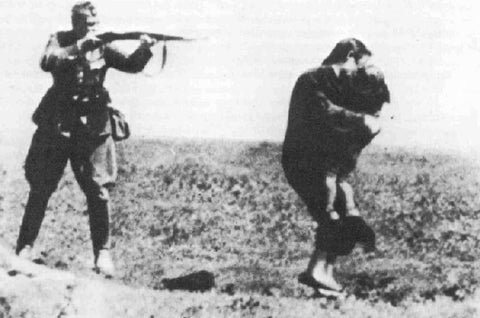 A greek soldier pointing the gun agains a Cham woman and her child