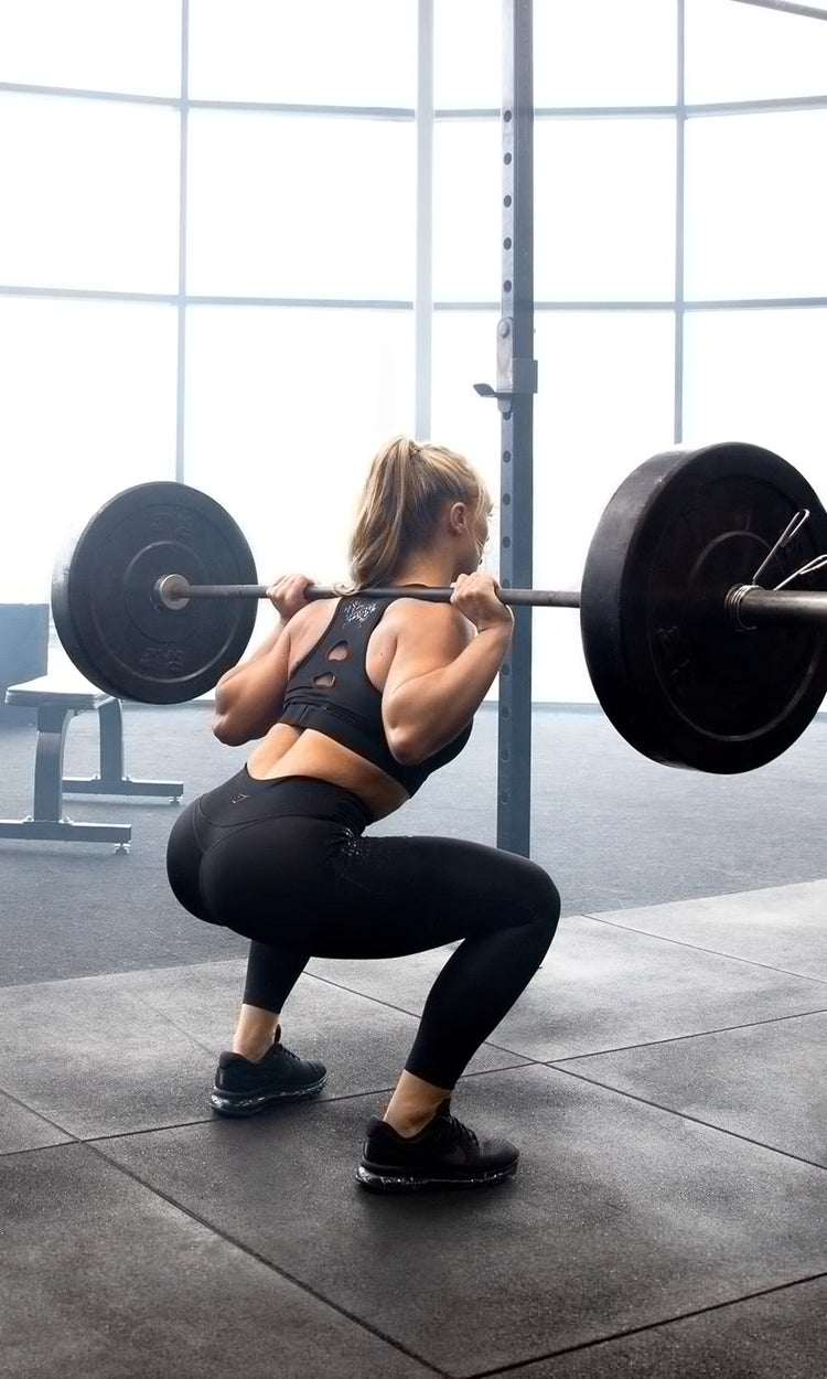 Gymshark athlete squatting demonstrating the silicone grip and bar on the upper back. Demonstrated in a bright natural light gym wearing the EXO collection.