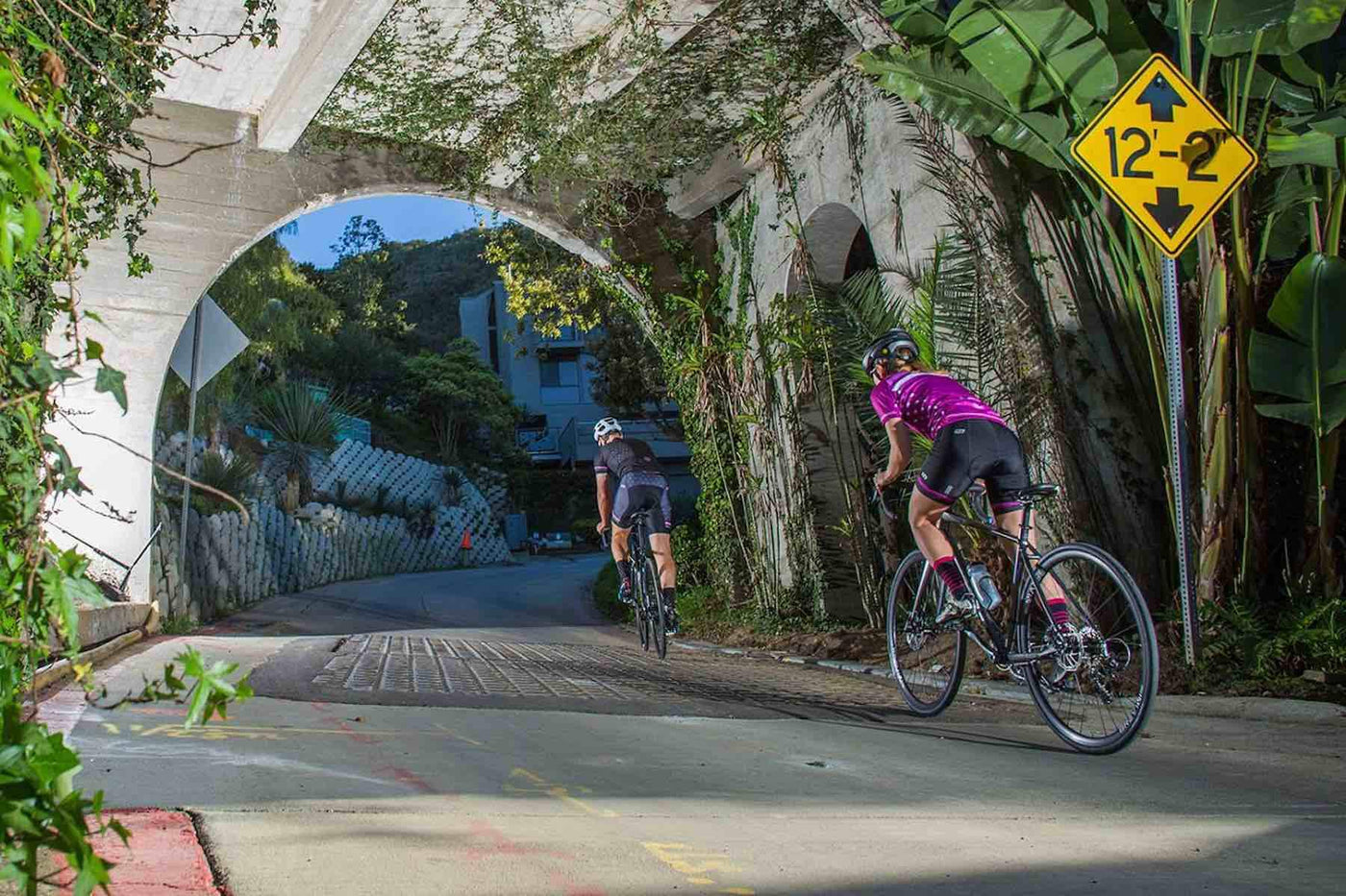 Two road bike riders riding through a bridge under path.