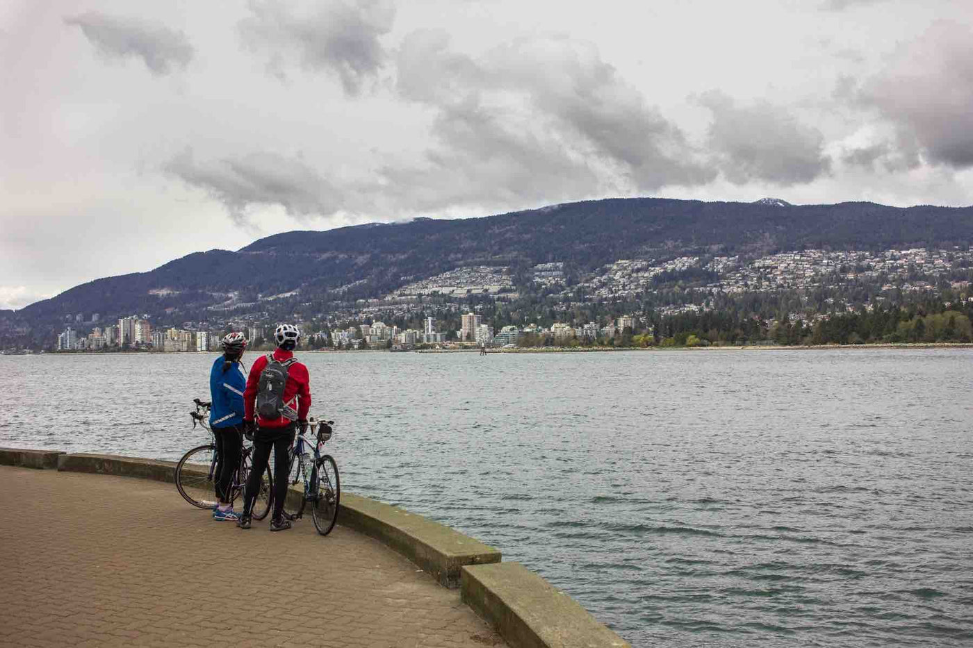 Two bike riders along a river edge enjoying the view of the water and the city skyline in the background..