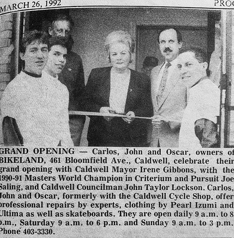 Picture of the Bikeland Grand Opening in 1992 with the owner and town officials in front of the bike shop cutting a ribbon to the entrance of the bike shop.