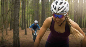A young woman and man couple mountain biking and enjoying themselves riding a trail through the woods.