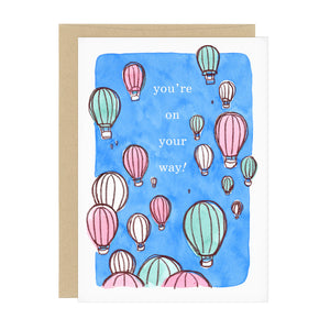 "Celebratory greeting card with lots of hot air balloons. Text reads: ""you're on your way!"""