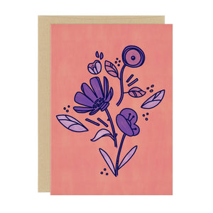 A greeting card with a motif of three purple flowers on a dusty pink background, with light purple accents
