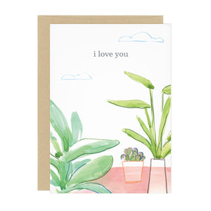 "Greeting card with illustration of three house plants on a pink table, with clouds in the sky. Text reads ""i love you"""