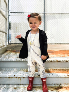 toddler-in-tie-dye-pants-romper-near-industrial-stairs