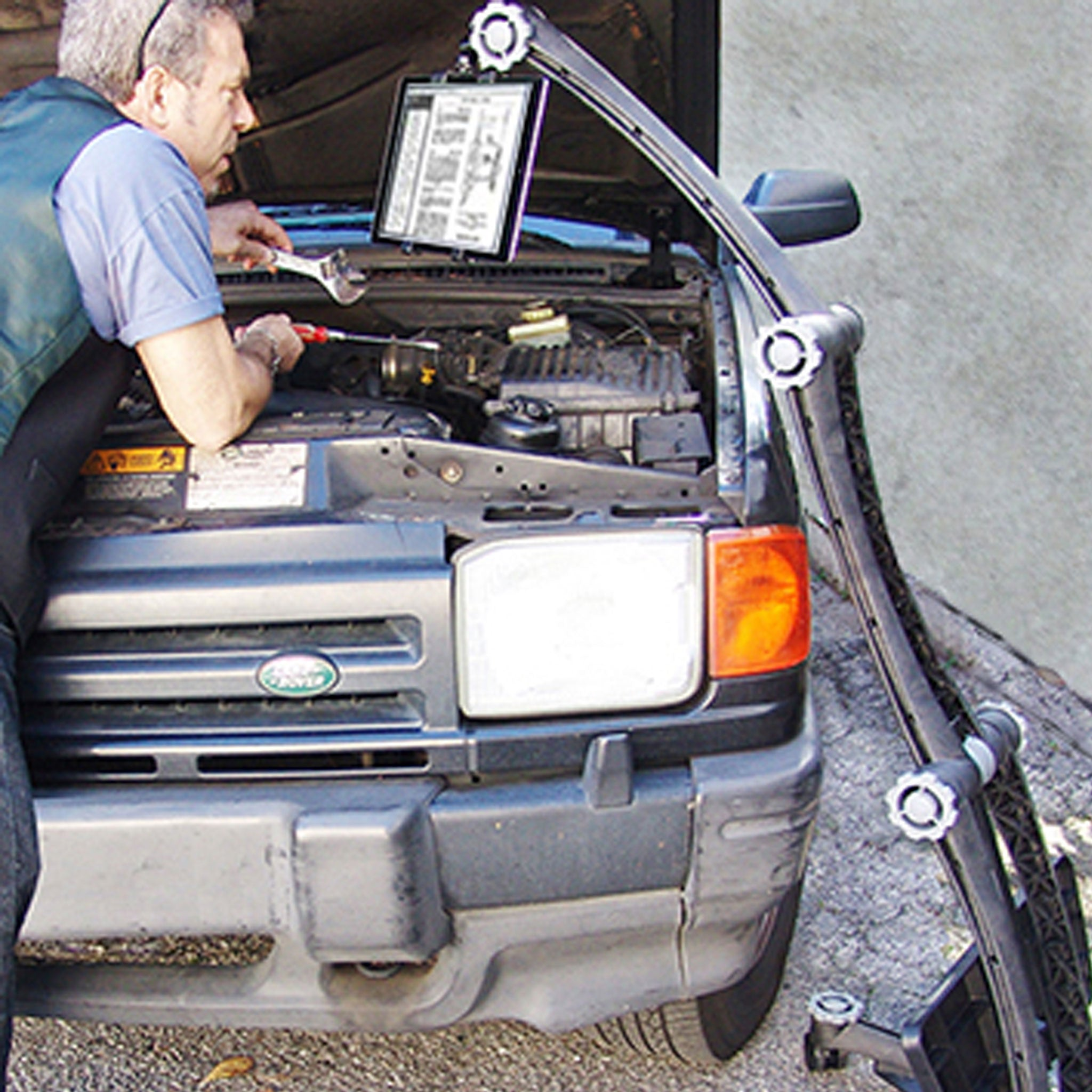 Image of a man performing repairs on his car using the ZStand AllStar to hold his iPad showing repair instructions.