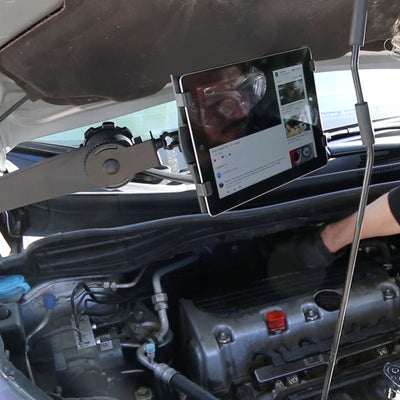 Image of a man using the ZStand AllStar to hold his tablet while he reads and performs car repairs.
