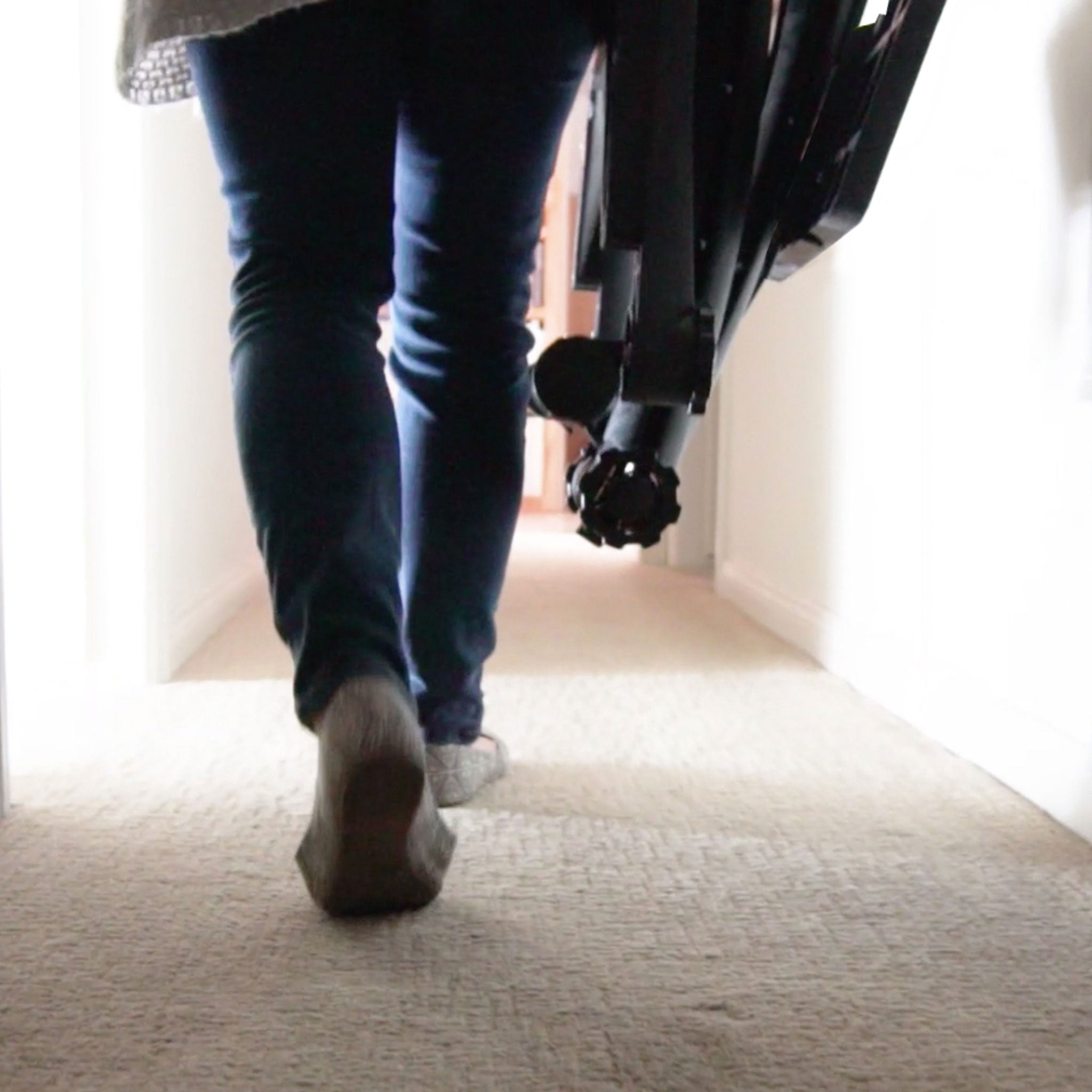 Image of a woman carrying her ZStand Double Decker through the hallway in her home.