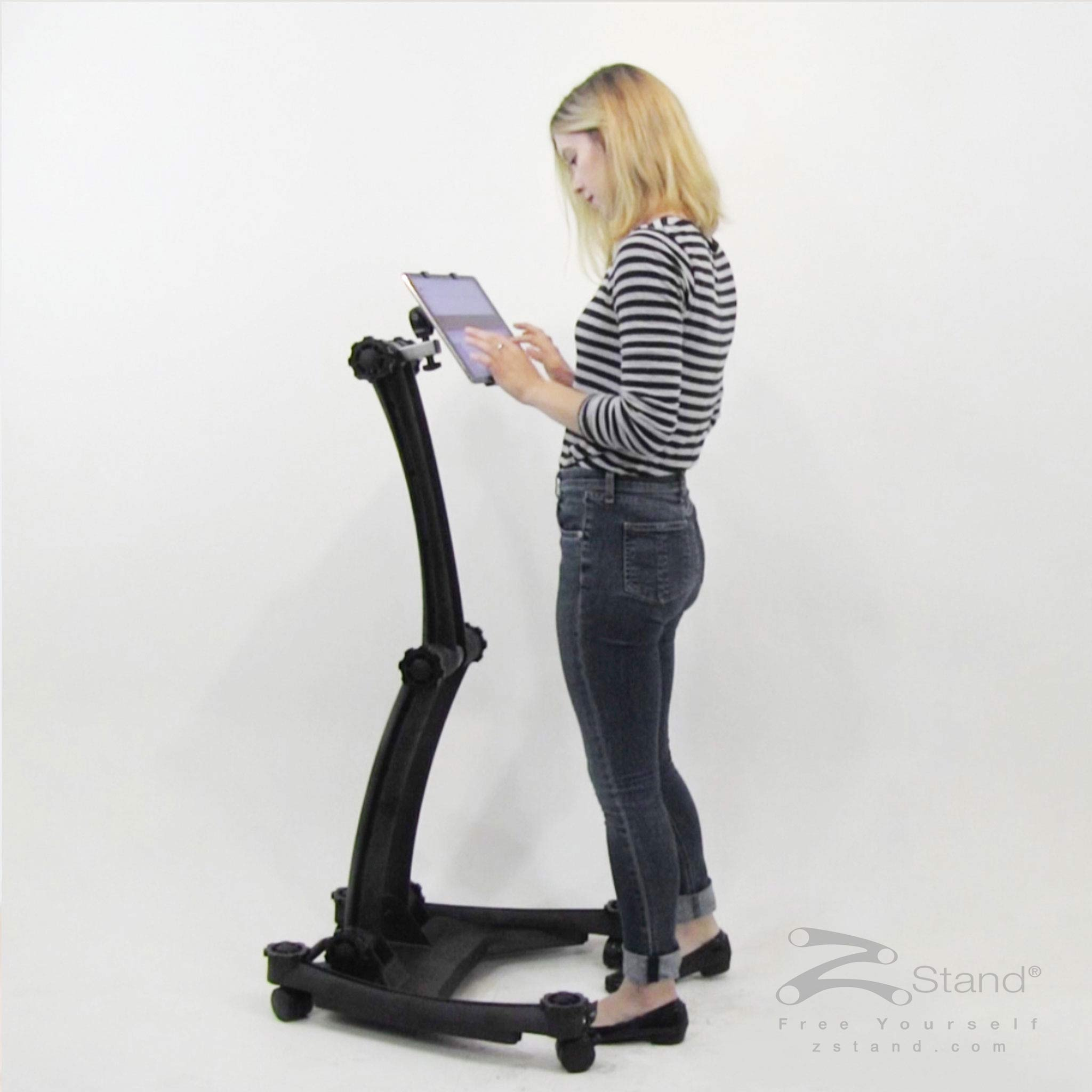 Image of a woman standing using her tablet hands free with the ZStand Sportster.