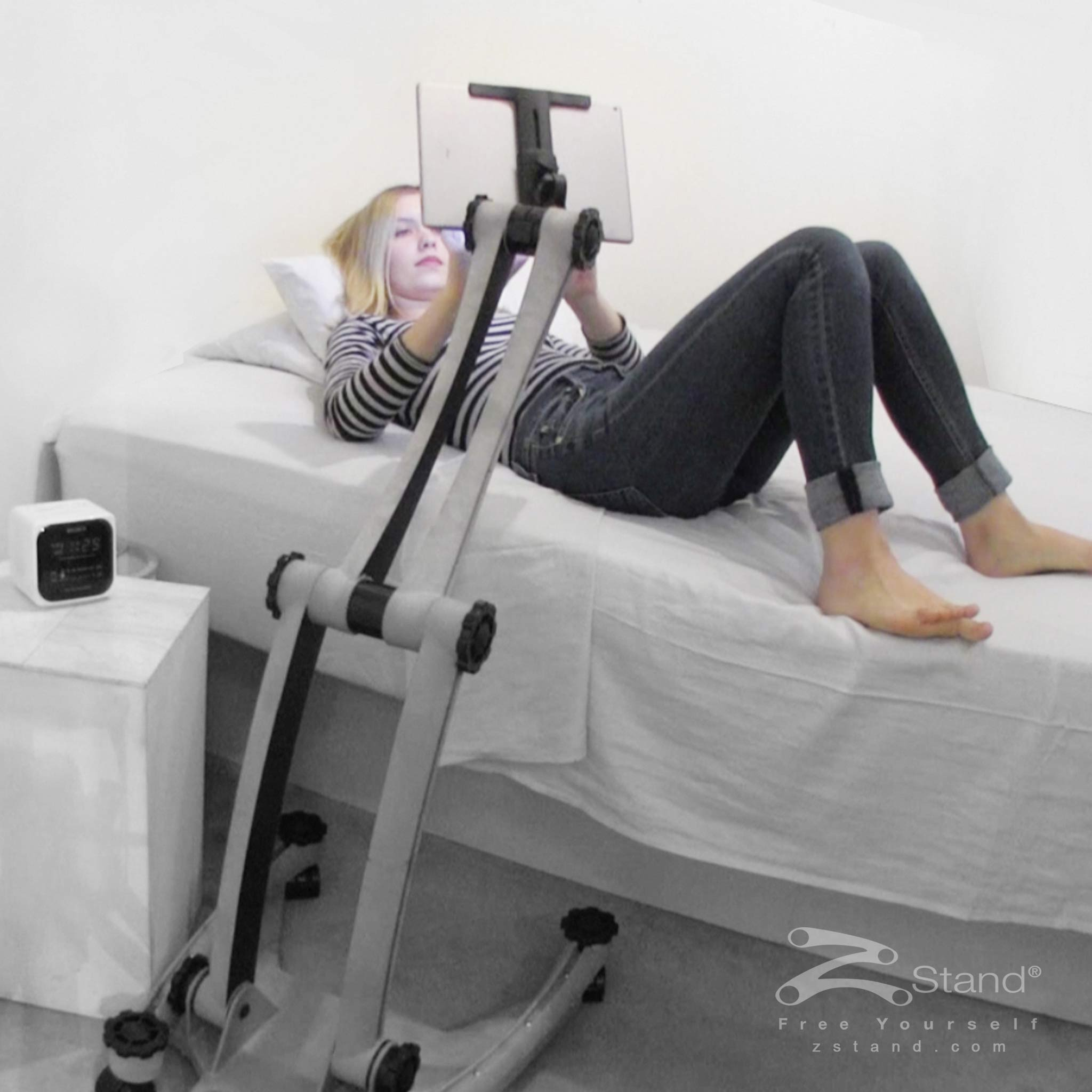 Image of a woman lying down in bed enjoying her tablet device hands free thanks to the ZStand Sportster.