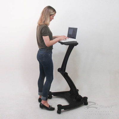 Image of a woman standing and doing work on her laptop thanks to the ZStand Sportster LT portable workstation