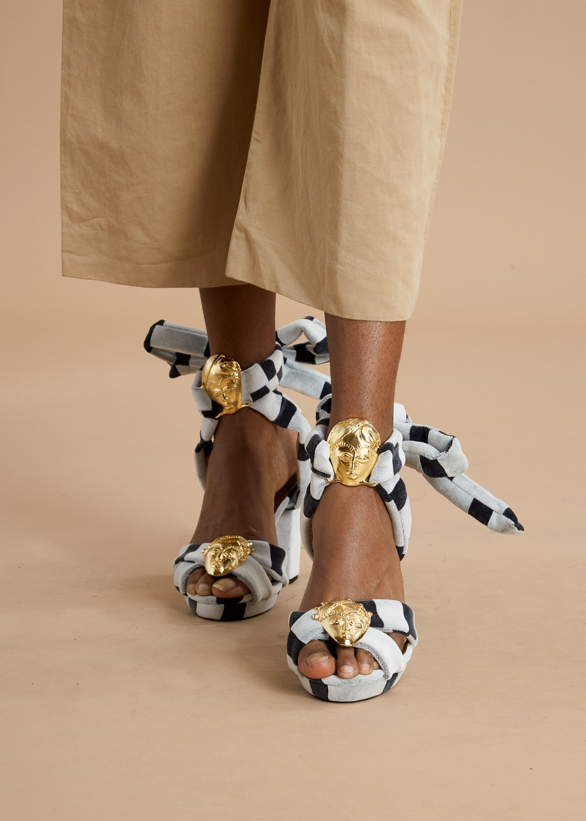 White and black striped high heel sandals with bronze masks