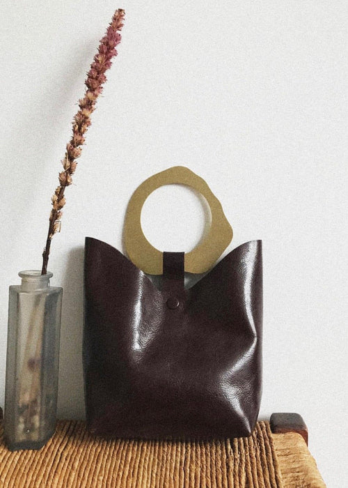 Small brown leather bag with brass handle