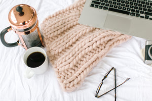Cozy in bed with coffee and laptop - distractions you could use right now
