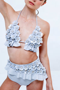 Floral High Waist Bikini White There is a thread of glamour in everything Badgley Mischka creates and this intricately designed, and beautifully crafted bikini is the embodiment of that. Brimming with floral details in the front and a simple ruffle that wraps around the back.