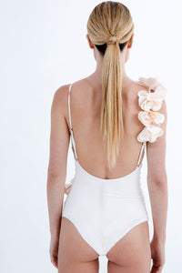Feminine one piece by Badgley Mischka features a beautifully laser-cut floral trim. The trim wraps from the adjustable strap around shoulder through the bodice, giving this classic silhouette an artistic uplift. Fully lined, Flower Trim Detail, Low Scrunch Back, High Cut leg, One Piece with adjustable straps swimsuit.