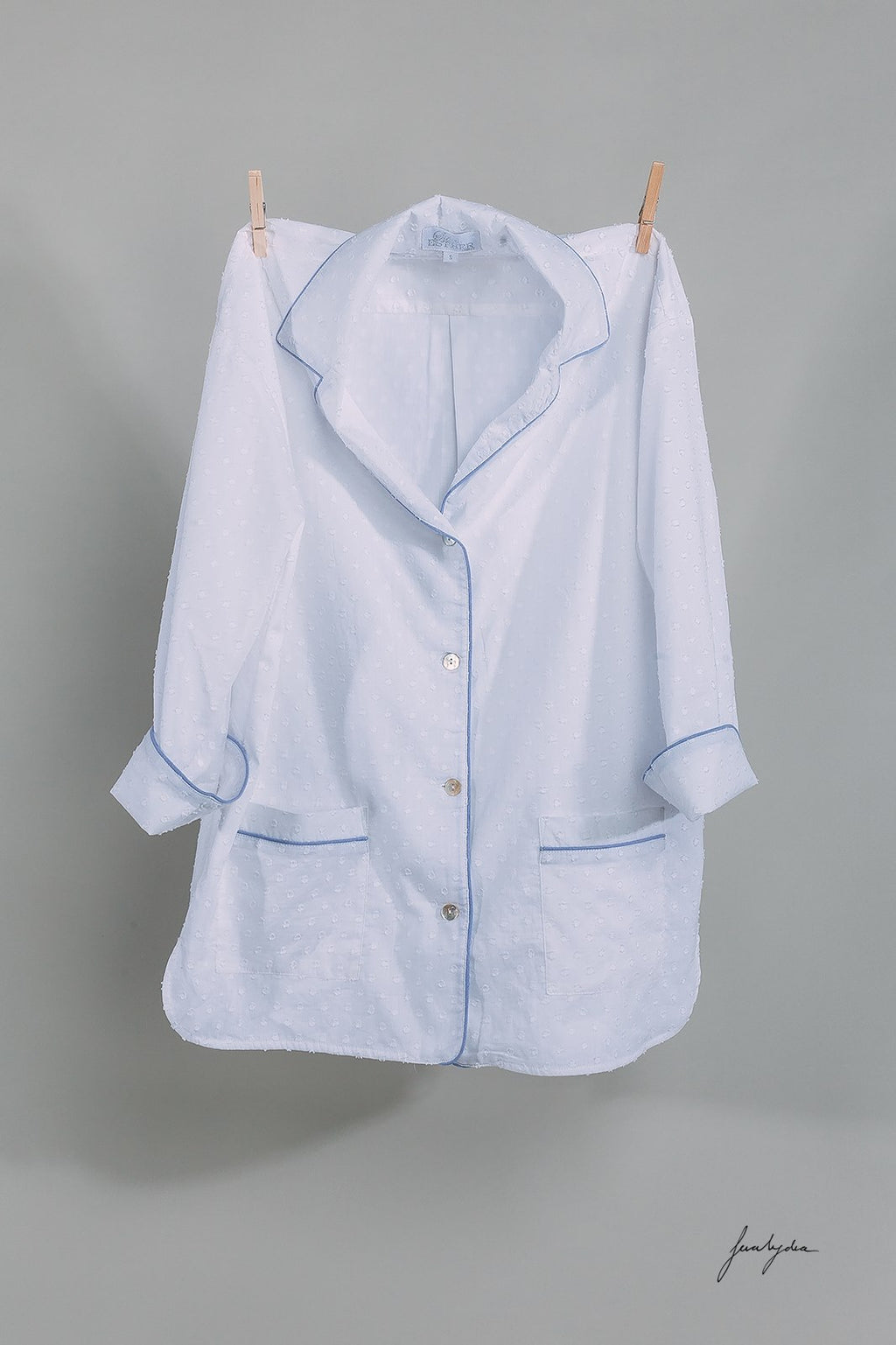 Luxury white cotton dobby long pyjama set with blue chambray piping. The pj set features Mother of Pearl buttons and pockets on the jacket. Ultimate luxury loungewear!