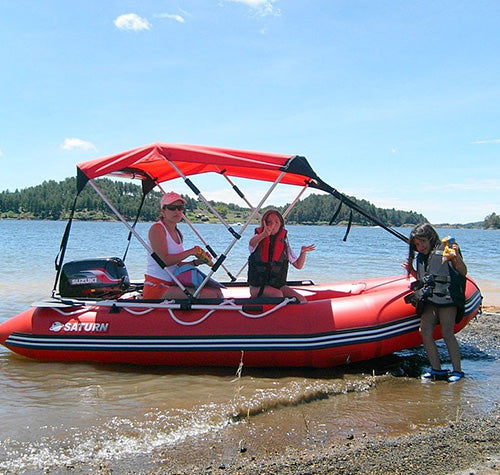 An Inflatable boat, this is a large Saturn inflatable motor boat with motor, boat canopy, oars, and life vest all on a lakeshore.
