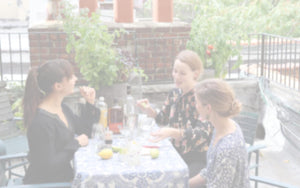 A group of women enjoy a balcony-grown beverage from a custom Seedsheet with cocktail herbs growing