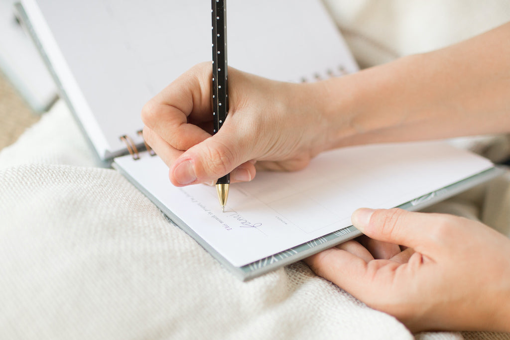 White woman's hand writing in a prayer journal that is spiral bound.