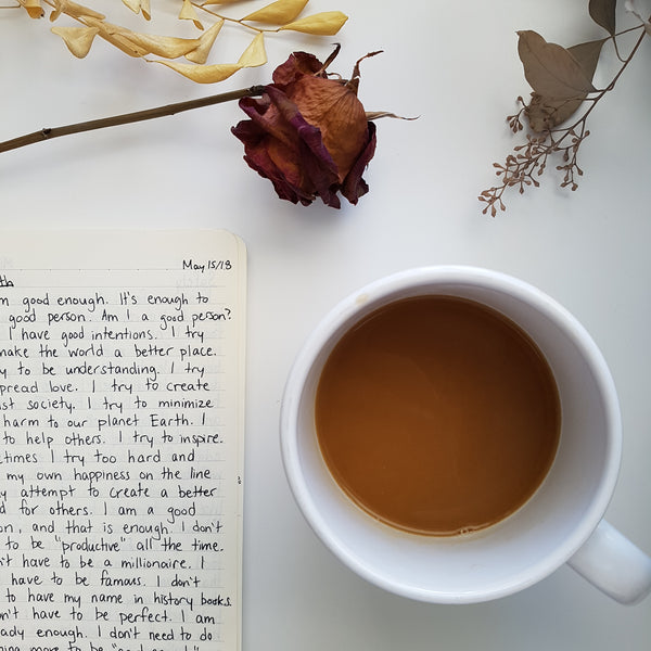 Image of a journal with positive affirmations next to a half-full coffee mug below some dried flowers