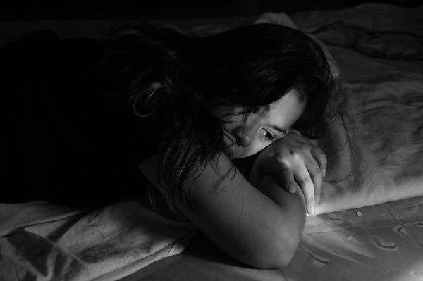 Greyscale image of woman lying on her stomach on a bad looking depressed