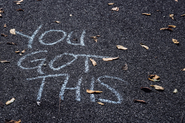 """You Got This"" written in chalk on an asphalt floor"