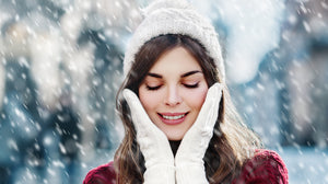 beautiful woman in the snow holding her face wearing a white hat and gloves