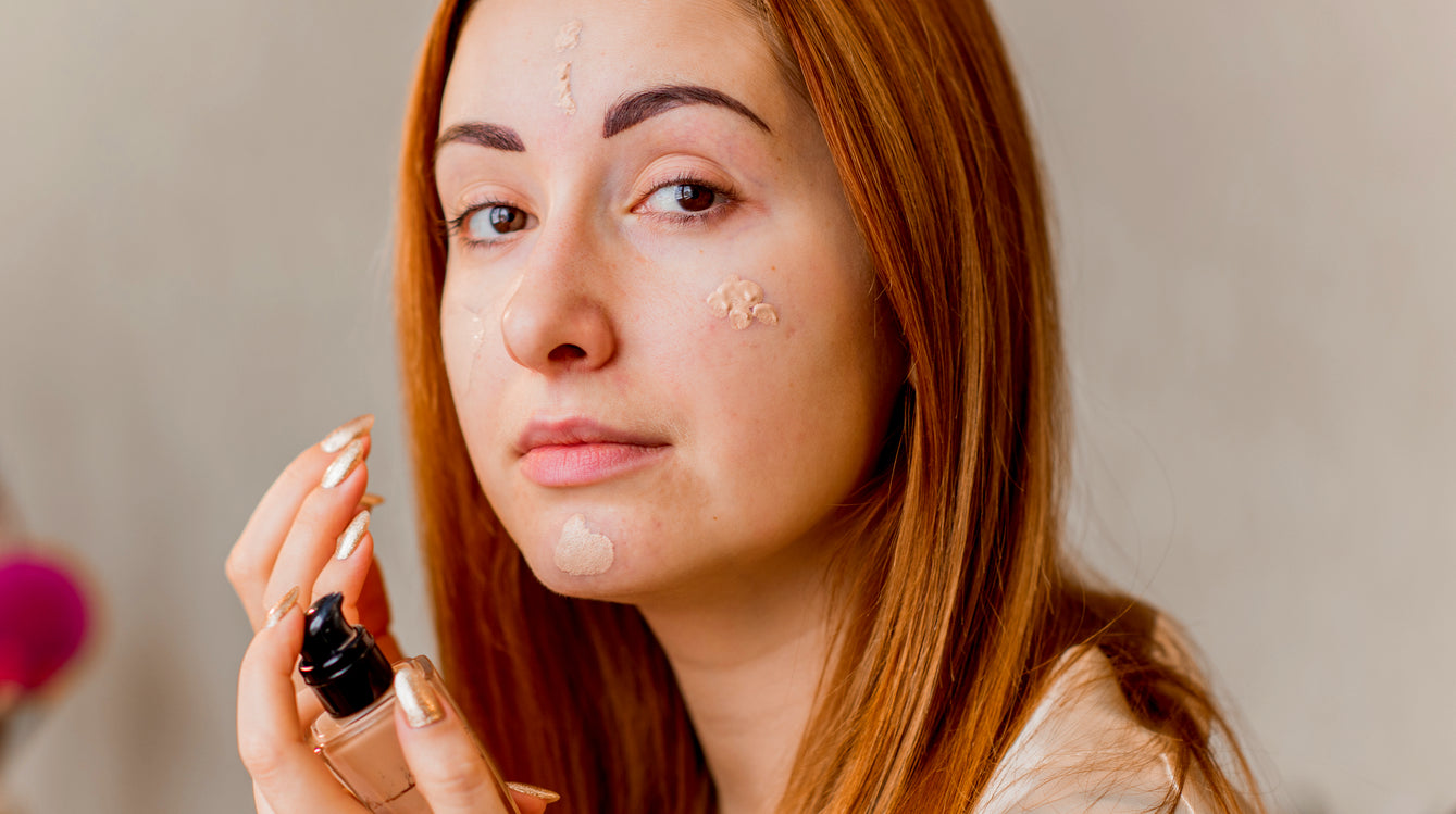 red headed women covering up dark marks on face with makeup