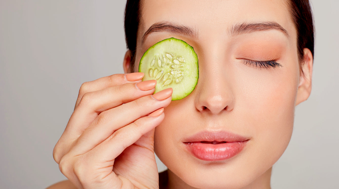 woman holding cucumber up to her eye